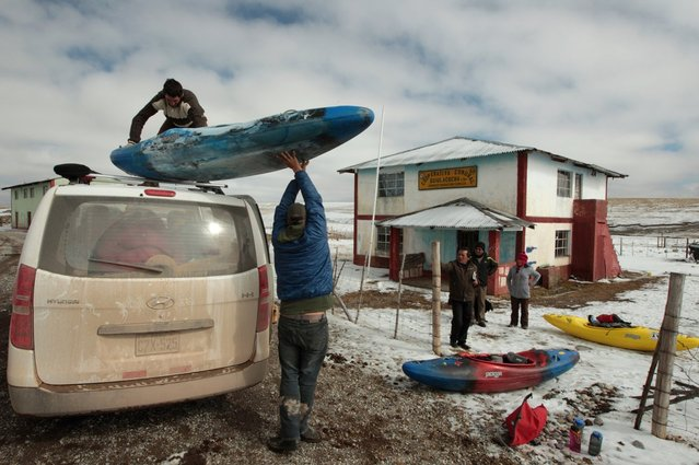 August 20, 2012 – Tombillo, Peru – Amazon Express white water team manager David Kelly passes up a kayak to Juan Antonio De Ugarte after the white water team's unscheduled stop. (Photo by Erich Schlegel/zReportage via ZUMA Press)