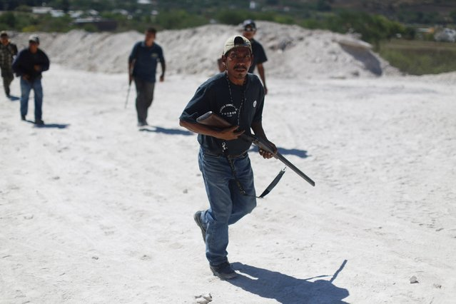 Members of the Community Police of the FUSDEG (United Front for the Security and Development of the State of Guerrero) patrol the village of Petaquillas, on the outskirts of Chilpancingo, in the Mexican state of Guerrero, February 1, 2015. (Photo by Jorge Dan Lopez/Reuters)