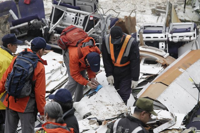 Rescue personnel examine the wreckage of TransAsia Airways plane Flight GE235 after it crash landed into a river, in New Taipei City February 5, 2015. (Photo by Pichi Chuang/Reuters)