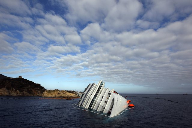 The Costa Concordia cruise ship which ran aground off the west coast of Italy at Giglio island lies on its side, half-submerged and threatening to slide into deeper waters in this January 23, 2012 file photo. (Photo by Tony Gentile/Reuters)