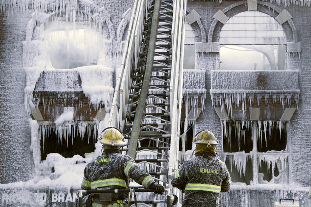 Philadelphia firefighters work the scene of an overnight blaze in west Philadelphia, Monday February 16, 2015, as icicles hang from where the water from their hoses froze. Bone-chilling, single digit temperatures have gripped the region, prompting the closure of all parish and regional Catholic elementary schools in the city of Philadelphia. (Photo by Jacqueline Larma/AP Photo)
