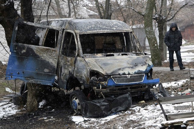 A man walks past a burnt vehicle, which according to locals was destroyed by a shelling, in Donetsk, eastern Ukraine February 9, 2015. (Photo by Alexander Ermochenko/Reuters)