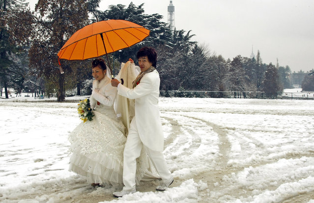 A newly wedded Chinese couple walks in the snow at a park in downtown Milan December 10, 2008. Italy has been struck by extreme weather this week, snowfall in the north, floods in Venice and strong winds fanning wildfires in the south. (Photo by Stefano Rellandini/Reuters)