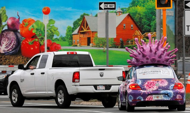 A car, advertising for Quidel Corp., which makes test kits for both the flu and the coronavirus disease (COVID-19), waits at a traffic light with a large model of the influenza virus on its roof, in Medford, Massachusetts, U.S., March 31, 2021. (Photo by Brian Snyder/Reuters)