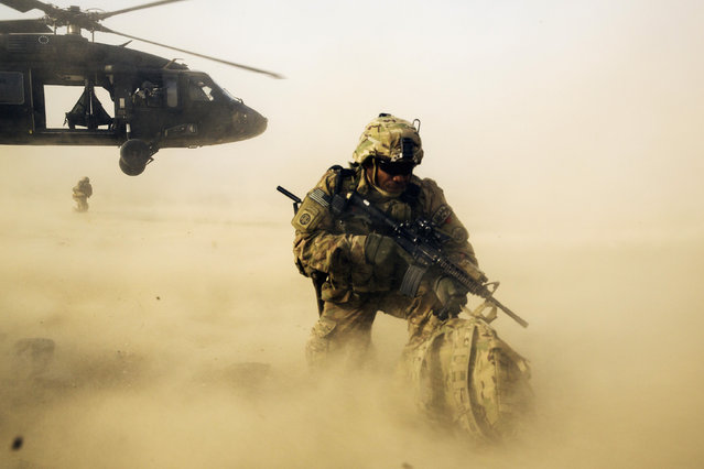 A U.S. soldier from the 3rd Cavalry Regiment shields himself from the rotor wash of a UH-60 Blackhawk helicopter after being dropped off for a mission with the Afghan police near Jalalabad in the Nangarhar province of Afghanistan on December 20, 2014. (Photo by Lucas Jackson/Reuters)