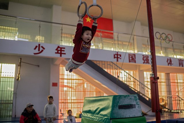 In this picture taken on January 12, 2021, a young gymnast trains at the Li Xiaoshuang Gymnastics School in Xiantao, Hubei province. (Photo by Nicolas Asfouri/AFP Photo)