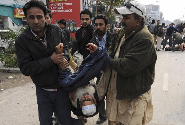 Residents carry an injured man from the site of an explosion outside the police headquarters, in Lahore February 17, 2015. (Photo by Imran Sheikh/Reuters)