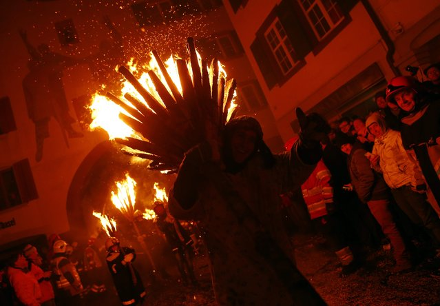 Carnival revellers carry burning wooden sticks as they take part in the traditional Swiss Chienbaese celebration in Liestal near Basel February 22, 2015. (Photo by Ruben Sprich/Reuters)