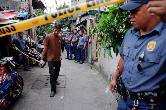 Police gather in an alley as the bodies of Noberto Maderal and fellow pedicab driver George Avancena, killed during a drug-related police operation, are taken by funeral parlour workers in Manila, Philippines October 19, 2016. (Photo by Damir Sagolj/Reuters)