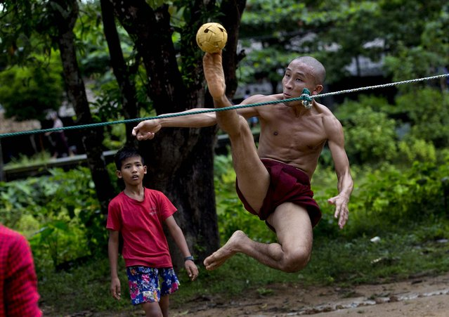 A Buddhist monk kicks a rattan ball during a game of Chinlone in Kawhmu, southwest of Yangon, Myanmar, on September 29, 2013. Chinlone, a combination of sport and dance, is played between two teams, each consisting of six players, passing a rattan ball back and forth with feet, knees and heads. (Photo by Gemunu Amarasinghe/Associated Press)