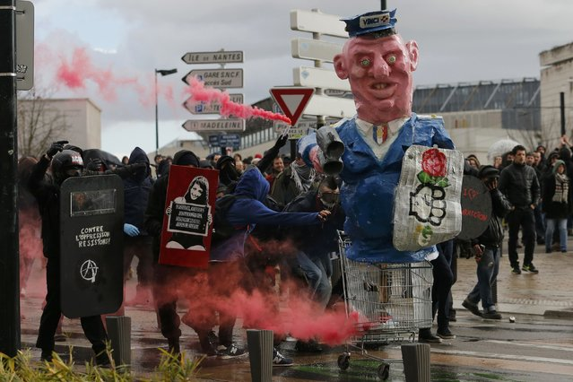 Masked protesters with safety flares take cover near a figure holding a French Socialist Party symbol during clashes at a demonstration to mark the one-year anniversary of a protest march in 2014 which ended in violence, in Nantes February 21, 2015. (Photo by Stephane Mahe/Reuters)