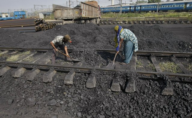 Workers clear a track in a railway coal yard on the outskirts of Ahmedabad, India, in this November 25, 2013 file photo. (Photo by Amit Dave/Reuters)