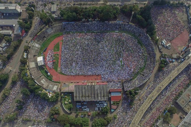 This aeriel view shows Muslim worshippers listening to the Eid al-Fitr morning prayer sermon at a soccer stadium in Addis Ababa, Ethiopia, on May 13, 2021 as Muslims across the globe mark the end of the Holy month of Ramadan. (Photo by Amanuel Sileshi/AFP Photo)