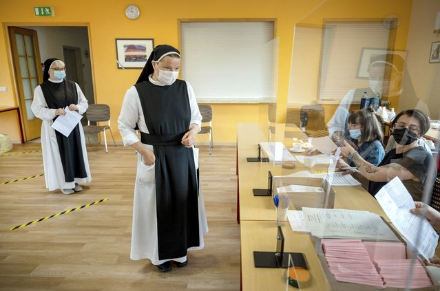 Sisters Pauline, left, and Gertrud from the Cistercian convent of Helfta  arrive at the polling station during the state elections of German federal state  Saxony-Anhalt, in the Helfta district of Eisleben, Germany, Sunday, June 6, 2021. The election for the new state parliament in Saxony-Anhalt is the last state election before the federal election in September 2021. (Photo by Hendrik Schmidt/dpa via AP Photo)