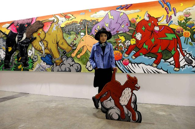 "Thailand artist Yuree Kensaku poses with her artwork ""When the Elephants Fight, the Grass Gets Trampled"" during the VIP preview of the art fair Art Basel in Hong Kong Friday, March 13, 2015. (Photo by Kin Cheung/AP Photo)"