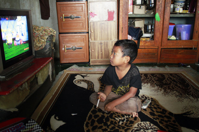 Dihan smokes as he watches television at his home. (Photo by Rezza Estily/JG Photo)