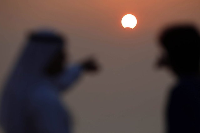 Kuwaiti men watch a partially solar eclipse at Souq Sharq Marina in Kuwait City on November 3, 2013. A rare solar eclipse will sweep across parts of Africa, Europe and the United States as the moon blocks the sun either fully or partially, depending on the location. (Photo by Yasser Al-Zayyat/AFP Photo)