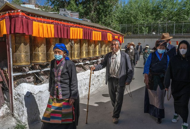 Tibetan Buddhists walk the kora at a local shrine during a government organized visit for journalists on June 3, 2021 in Lhasa, Tibet Autonomous Region, China. Travel restrictions for foreign travellers were recently loosened in a bid to boost tourism to Tibet. Chinas government is aiming for 61 million visitors annually by 2025, more than 15 times the number of Tibets inhabitants. Foreign journalists, normally not permitted to travel to the autonomous region, were recently taken on a government-organized visit. (Photo by Kevin Frayer/Getty Images)