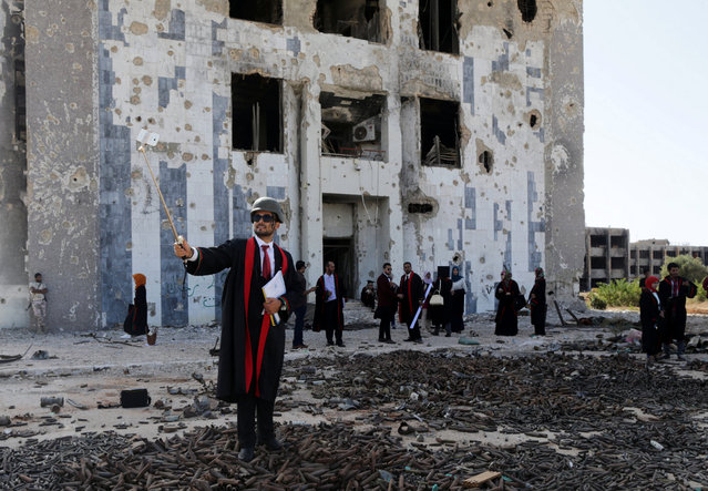 LIBYA: A new graduate of Benghazi University takes a selfie in front of a ruined building at his university former headquarters which was destroyed during clashes in 2014 between members of the Libyan National Army and Shura Council of Libyan Revolutionaries, an alliance of former anti-Gaddafi rebels who have joined forces with Islamist group Ansar al-Sharia, in Benghazi, Libya, October 27, 2016. (Photo by Esam Omran Al-Fetori/Reuters)