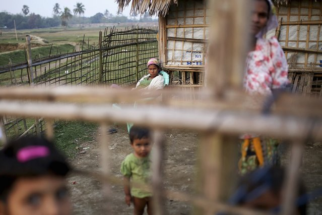 Internally displaced Rohingya women and children look from behind the fence of their temporary home at Thae Chaung IDP camp on the outskirts of Sittwe, February 15, 2015. (Photo by Reuters/Minzayar)