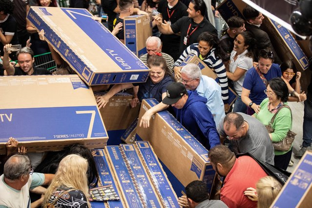 People buy televisions at a supermarket  during a Black Friday sale in Sao Paulo, Brazil, 22 November 2018. Black Friday is an day following Thanksgiving Day , annually held on the fourth Thursday in November, in the United States and generally marks the beginning of the Christmas shopping season. (Photo by Sebastiao Moreira/EPA/EFE)