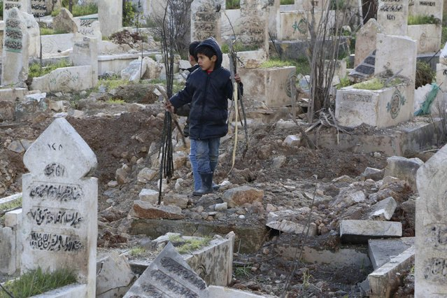 A boy collects firewood amid graves damaged by what activists said were barrel bombs dropped by forces loyal to Syria's President Bashar al-Assad in Old Aleppo's Kadi Askar area January 9, 2015. (Photo by Mahmoud Hebbo/Reuters)