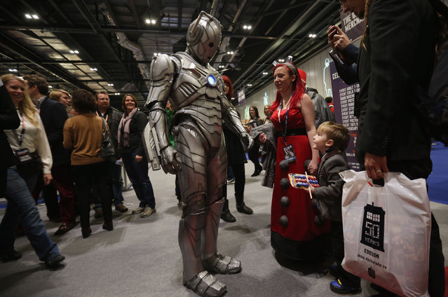 """Doctor Who fans meet an actor dressed as a """"Cyberman"""" at the """"Doctor Who 50th Celebration"""" event in the ExCeL centre on November 22, 2013 in London, England. (Photo by Oli Scarff/Getty Images)"""