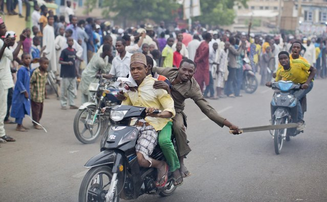A supporter of opposition candidate Muhammadu Buhari riding on a motorcycle scrapes a machete on the ground to create sparks and noise, in celebration of an anticipated win for his candidate, in Kano, Nigeria Tuesday, March 31, 2015. (Photo by Ben Curtis/AP Photo)