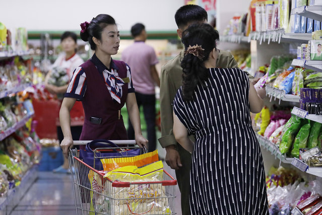 In this September 12, 2018 photo, North Korean customers get assistance at a supermarket in Pyongyang, North Korea. In the era of Kim Jong Un, North Korea is learning to embrace its inner consumer. The rise of the consumer is a major feature, not a bug, of Kim's plans to strengthen the country's sad-sack economy and lift the people's standard of living. How far will it be allowed to go? That's hard to say. But Kim has big plans for the economy of his country and, for now at least, the regime's calculus appears to be that greater economic activity will translate into more money flowing into its own coffers to help fund those plans. (Photo by Kin Cheung/AP Photo)
