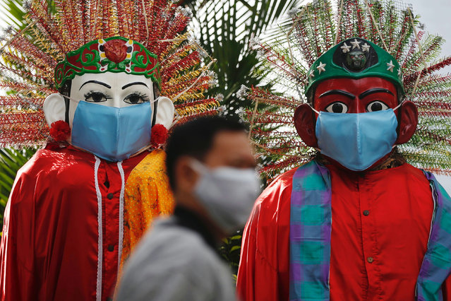 """A man wearing a protective face mask walks past traditional large puppet figures called """"Ondel-ondel"""", also donning face masks and displayed along a sidewalk of a main road, as coronavirus disease (COVID-19) cases surge in Jakarta, Indonesia, June 30, 2021. (Photo by Willy Kurniawan/Reuters)"""