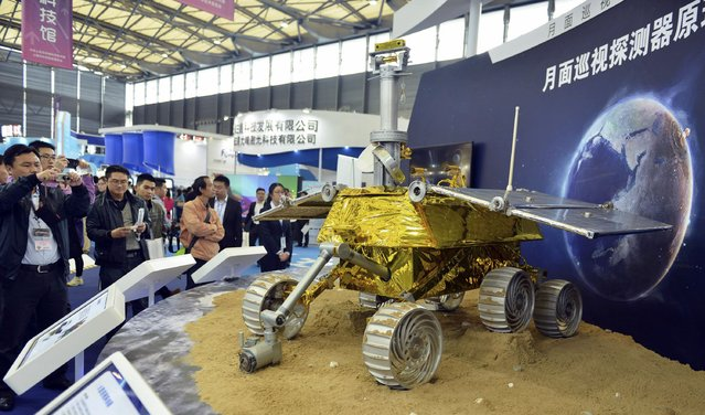 Visitors take pictures of a prototype model of a lunar rover at the 15th China International Industry Fair in Shanghai, November 5, 2013. China will land its first probe on the moon in early December which will deploy a buggy to explore its surface, an official said on November 26, marking a major milestone in the country's space ambitions. (Photo by Reuters/Stringer)