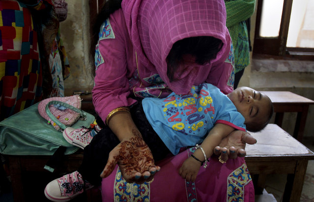 A Christian woman holds her child while she prays during Easter service at St. Oswald's Church in Lahore, Pakistan, Sunday, April 5, 2015. (Photo by K. M. Chaudary/AP Photo)