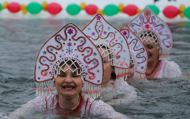 Participants wearing Kokoshnik, the Russian traditional headwear, perform during winter swimming festival in the town of Podolsk, south of Moscow, Russia January 5, 2017. (Photo by Maxim Shemetov/Reuters)