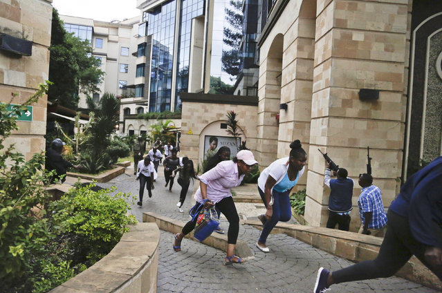 """Civilians flee as security forces aim their weapons at a hotel complex in Nairobi, Kenya Tuesday, January 15, 2019. Extremists launched a deadly attack on a luxury hotel in Kenya's capital Tuesday, sending people fleeing in panic as explosions and heavy gunfire reverberated through the complex. A police officer said he saw bodies, """"but there was no time to count the dead"""". (Photo by Khalil Senosi/AP Photo)"""