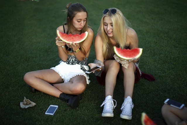 Women eat watermelons at the Coachella Valley Music and Arts Festival in Indio, California April 10, 2015. (Photo by Lucy Nicholson/Reuters)