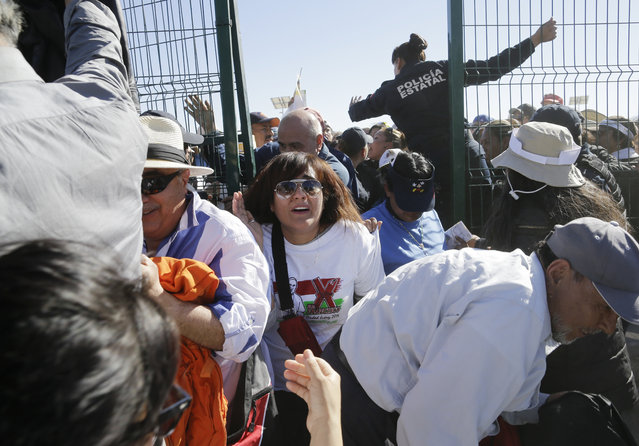 People push forward as they enter the area where Pope Francis will celebrate an outdoor Mass, in Ciudad Juarez, Mexico, Wednesday, February 17, 2016. Just before the start of his Mass in a large field in Juarez, Francis is expected to make a short walk to the border fence along the Rio Grande. (Photo by Gregory Bull/AP Photo)