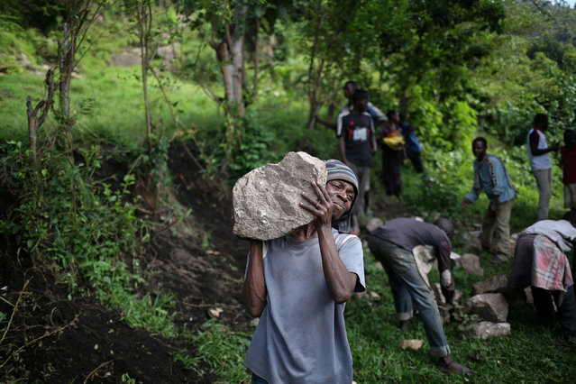 Ahadi, 23, carries heavy stones intended for the construction of an hotel in a village near Kagorwa Pygmy camp on Idjwi island in the Democratic Republic of Congo, November 25, 2016. Ahadi works for a Bahavu landlord and earns 500 CDF (0.46 USD) per day. (Photo by Therese Di Campo/Reuters)
