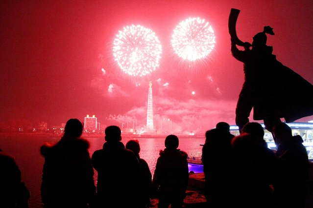 Fireworks explode over Juche Tower and the Taedong River in Pyongyang, North Korea to celebrate the New Year on Wednesday, January 1, 2014. (Photo by Kim Kwang Hyon/AP Photo)