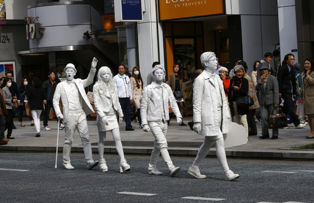 "Members of the human statue street performer group named ""Tokyo Hack"" get shoppers' attention as they march in Tokyo's Ginza shopping district Sunday, April 12, 2015. The main street in Ginza shuts the traffic and opens for shoppers during the day on Sundays. (Photo by Shizuo Kambayashi/AP Photo)"
