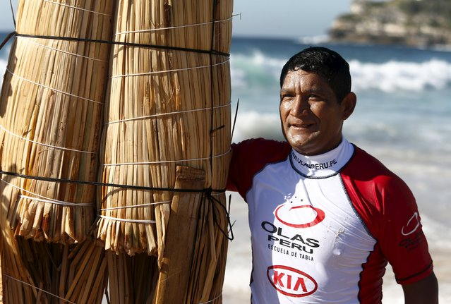 "Peruvian surfer Carlos ""Huevito"" Areola stands alongside his hand-made reed board, or ""caballito"" (little horse), following a surf at Sydney's Bondi Beach, February 24, 2016. (Photo by Jason Reed/Reuters)"