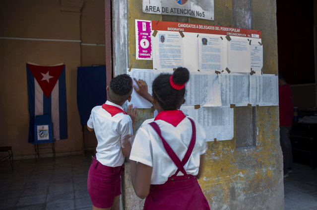 School children look at the list of voters at a polling station in Havana, Cuba, Sunday, April 19, 2015. (Photo by Ramon Espinosa/AP Photo)