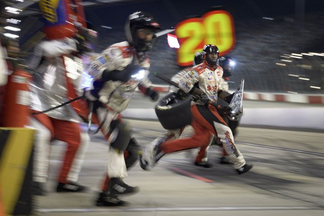 Crew members work a pit stop as Cristopher Bell comes in during a NASCAR Cup Series auto race Sunday, September 5, 2021, in Darlington, S.C. (Photo by John Amis/AP Photo)
