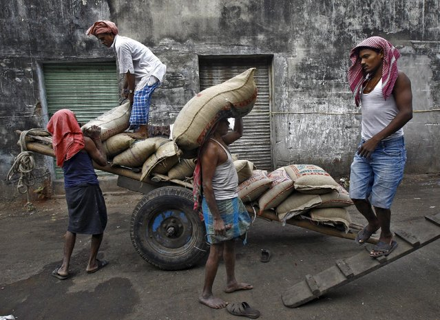 Labourers unload sacks of rice from a handcart at a wholesale market in Kolkata, India, in this December 14, 2015 file photo. (Photo by Rupak De Chowdhuri/Reuters)