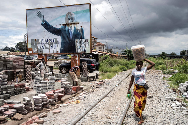 A woman walks past a torn billboard of former President of Guinea, Alpha Conde, in Conakry on September 16, 2021. Colonel Mamady Doumbouya's special forces on September 5, 2021 seized Alpha Conde in a Coup, the West African state's 83-year-old president, a former champion of democracy accused of taking the path of authoritarianism. (Photo by John Wessels/AFP Photo)