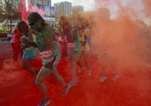Joggers run through coloured powder thrown by race marshalls during the Manila Color Challenge in Pasay city, metro Manila April 19, 2015. (Photo by Romeo Ranoco/Reuters)