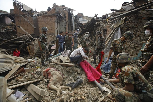 A dead body of a woman is seen after rescue workers recovered it from debris following Saturday's earthquake in Bhaktapur near Kathmandu, Nepal, Sunday, April 26, 2015. (Photo by Niranjan Shrestha/AP Photo)