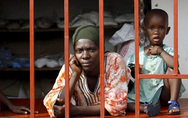 A shopkeeper and her child look through the grill in front of their stall during protests against the decision made by Burundi's ruling National Council for the Defence of Democracy-Forces for the Defence of Democracy (CNDD-FDD) party to allow President Pierre Nkurunziza to run for a third five-year term in office, in the capital Bujumbura, April 26, 2015. (Photo by Thomas Mukoya/Reuters)