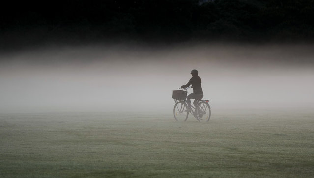 A woman rides her bicycle through a heavy mist in a park as the sun rises in Sydney, Australia, Tuesday, May 25, 2021. (Photo by Mark Baker/AP Photo)