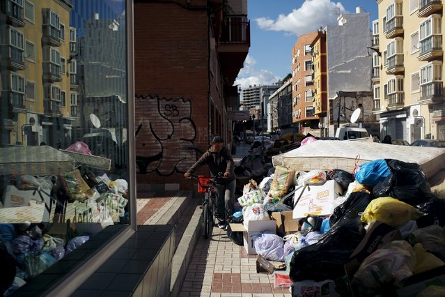 A woman walks with her bicycle past a pile of rubbish bags in a street during a strike by garbage collectors from waste management company Limasa, who have been on strike since March 1 against wage cuts, and to demand better working conditions in Malaga, southern Spain, March 10, 2016. (Photo by Jon Nazca/Reuters)
