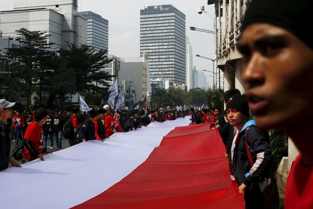 People carry a national flag as they march during a May Day rally in Jakarta, Indonesia, May 1, 2015. (Photo by Reuters/Beawiharta)